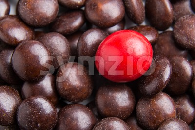 Focus on red chocolate candy against heaps of brown candies Stock Photo