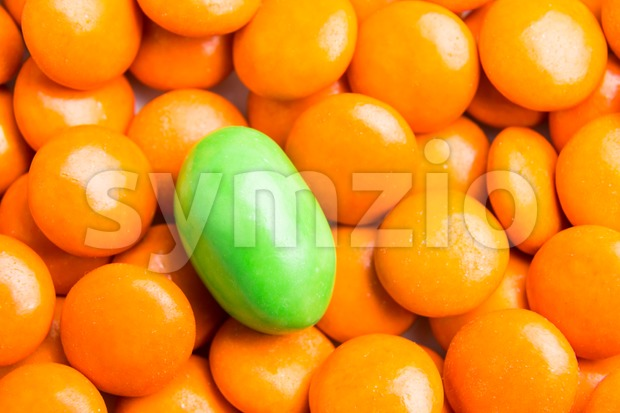 Concept of selective focus on green chocolate candy against heaps of orange candies in background