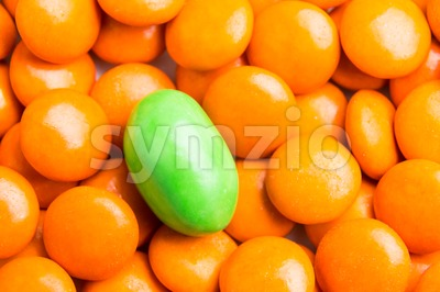 Focus on green chocolate candy against heaps of orange candies Stock Photo