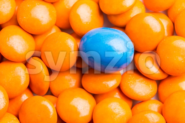 Concept of selective focus on blue chocolate candy against heaps of orange candies in background