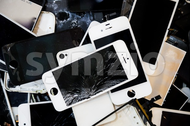 Stack and piles of damaged smart phone body and cracked LCD screen Stock Photo