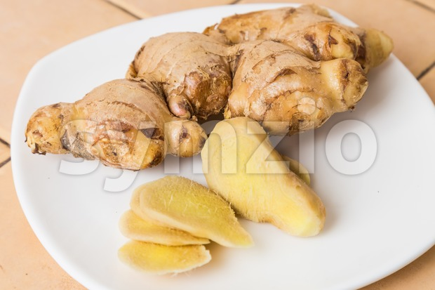 Whole and sliced revitalizing and aromatic ginger roots served on a plate Stock Photo