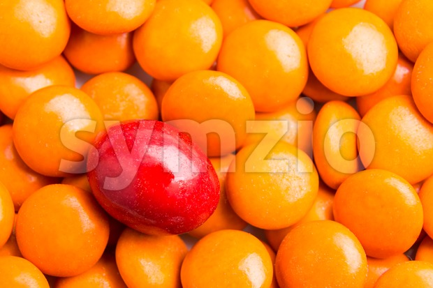Focus on red chocolate candy against heaps of orange candies Stock Photo