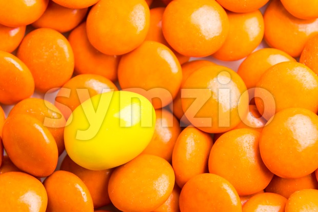 Concept of selective focus on yellow chocolate candy against heaps of orange candies in background