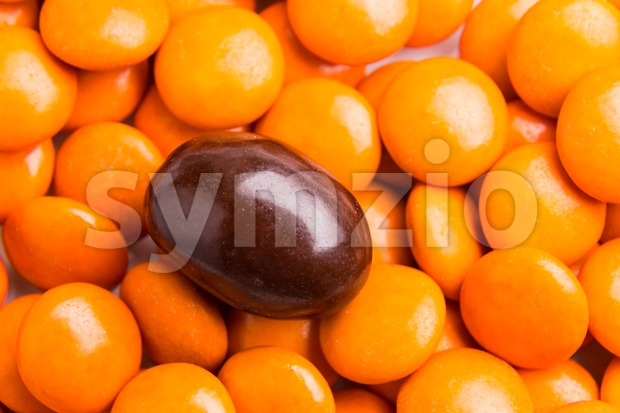 Concept of selective focus on brown chocolate candy against heaps of orange candies in background