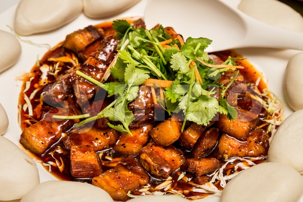 Delicious Chinese Stewed Pork Dish served with buns Stock Photo