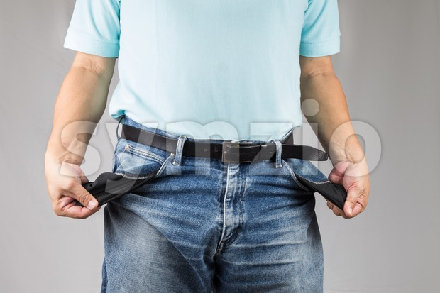 Depressed man in jeans pull out and show his empty pants pockets Stock Photo