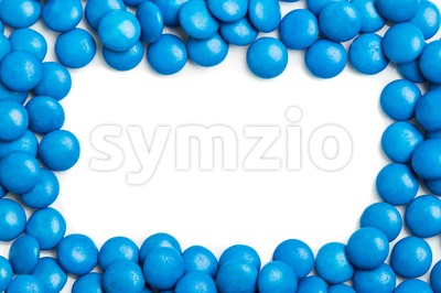 Frame of blue chocolate candy on white background with space Stock Photo