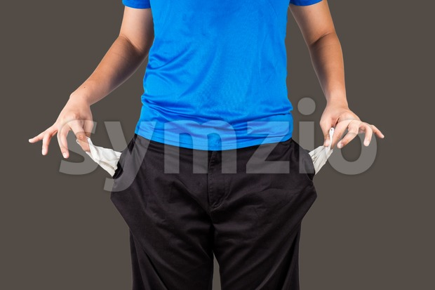 Teenager pull out and show his empty pants pockets with dark background Stock Photo