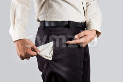 Man pull out and point at his empty pants pockets Stock Photo