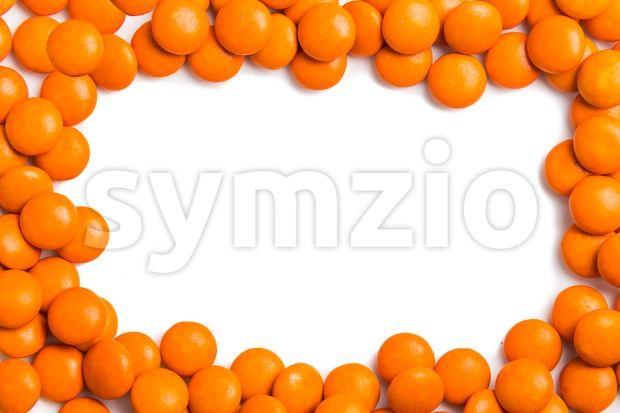 Frame of orange chocolate candy on white background with space Stock Photo