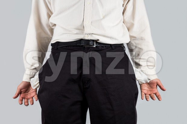 Depressed man with empty pants pockets gestures with both hands