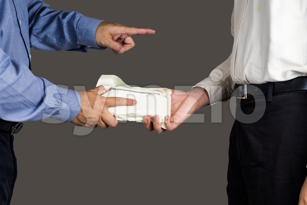 Man handling an envelope full of money to another person while pointing his finger Stock Photo