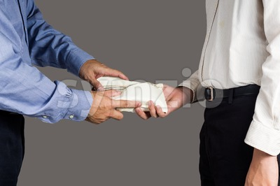 Man handling an envelope full of money to another person Stock Photo