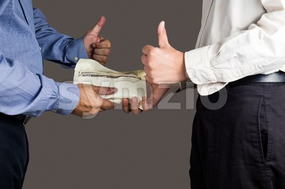 Man handling an envelope full of money to another person while making thumb up sign Stock Photo