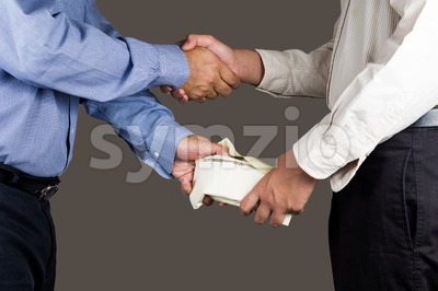 Man handling an envelope full of money to another person while shaking hands Stock Photo