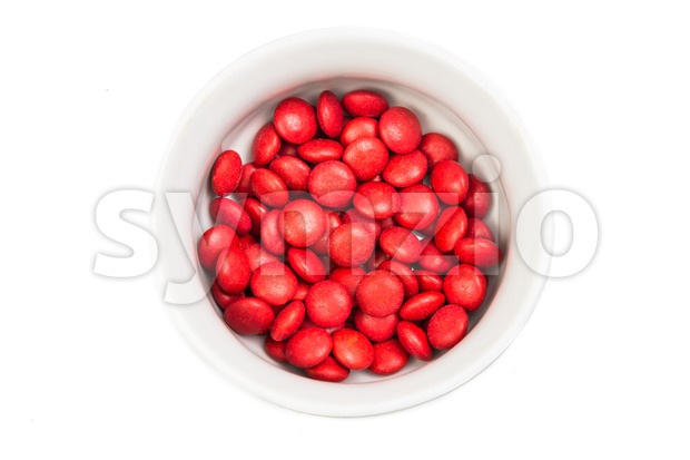 Overhead view bowl of red chocolate candy in white background Stock Photo