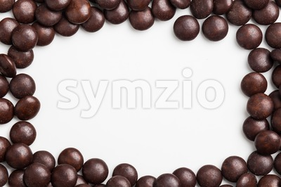 Frame of brown chocolate candy on white background with space Stock Photo