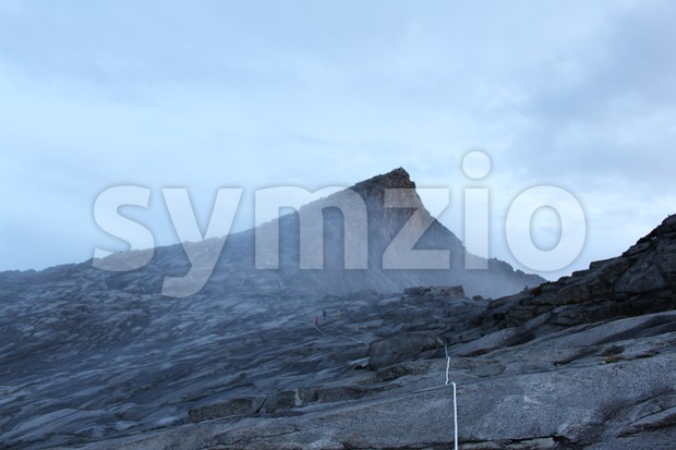 Mount Kinabalu Low's Peak in the morning with thick mist Stock Photo