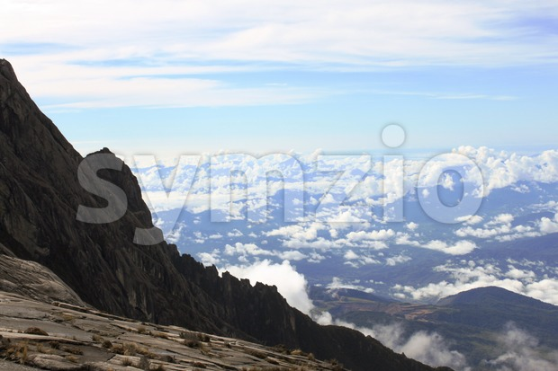 Steep ascending trail of Mount Kinabalu to the summit with serene blue sky and cloud at the background Stock Photo