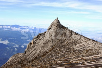 Majestic and iconic Mount Kinabalu South Peak against scenic blue sky Stock Photo