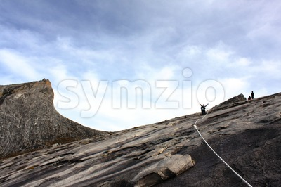 Two hikers in silhouette raised their hands whilst ascending the summit of Mount Kinabalu. Low's Peak is visible on the left. Stock Photo