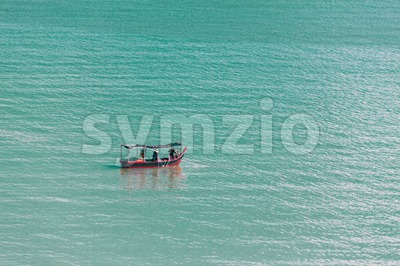 Fishermen on boat in the open sea fishing Stock Photo