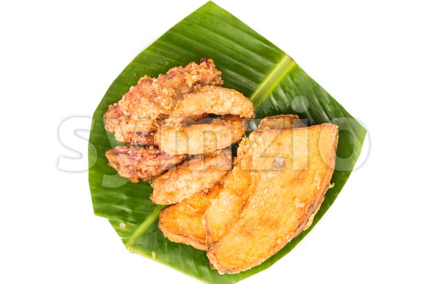 A serving consisting of the combination of fried banana (pisang goreng), fried sweet potatoes (keledek goreng) and fish nuggets (keropok lekor), a Stock Photo