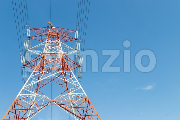 Red and white electricity pylon against blue sky Stock Photo