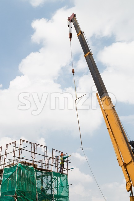 Construction of a mass transit train line in progress with an unidentifiable worker receiving a metal rod from a crane. Stock Photo