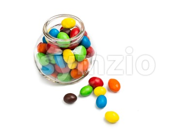 Transparent glass jar with colorful chocolate candies on white background Stock Photo