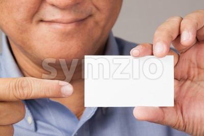 Smiling male Asian model pointing blank placard Stock Photo
