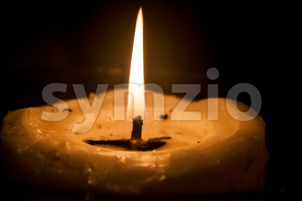 Single candle light illuminates a dark surrounding Stock Photo