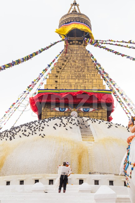 Devotee worshiping the sacred Boudhanath Stupa in Kathmandu, Nepal Stock Photo
