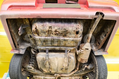 Car with rusty, damaged, corroded undercarriage at workshop for repair Stock Photo
