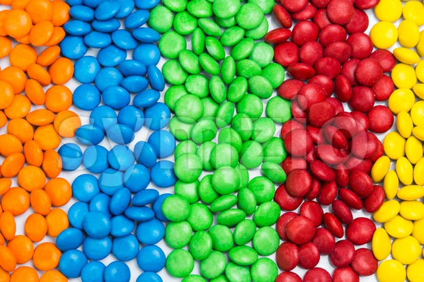 Pile of colorful chocolate candy by color in rows columns Stock Photo