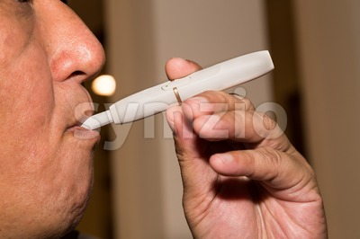 Smoker smoking hybrid smokeless cigarette device that uses real tobacco Stock Photo
