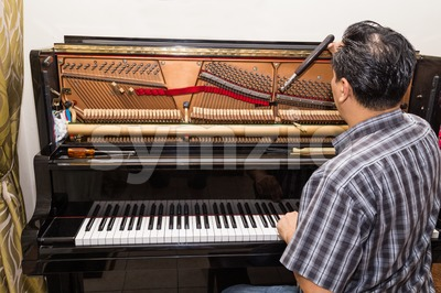 Technician tuning a upright piano using lever and tools Stock Photo