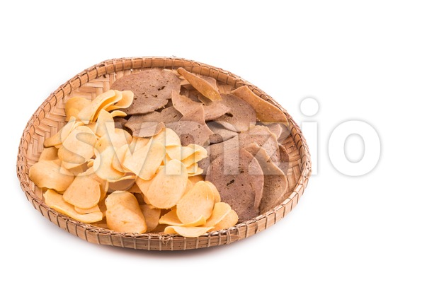 Dried raw prawn and fish crackers on traditional rattan tray Stock Photo