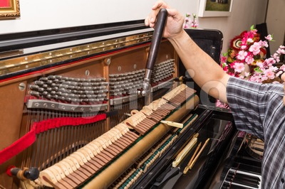 Closeup on hand tuning a upright piano using lever and tools Stock Photo