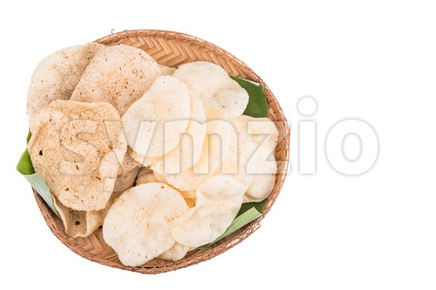 Freshy fried delicious prawn and fish crackers snack served on rattan tray with white background