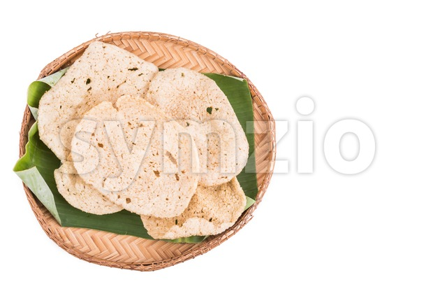 Freshy fried delicious fish crackers snack served on traditional rattan tray with white background