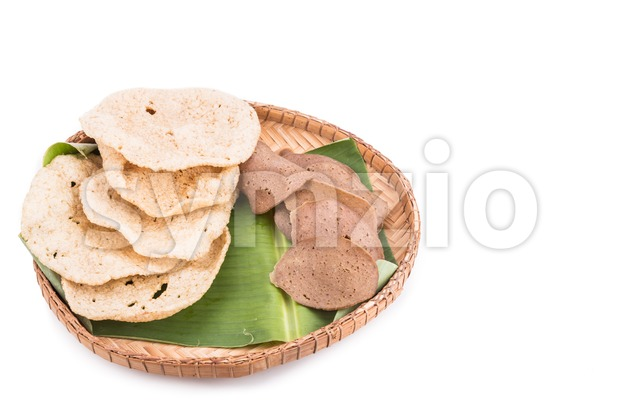 Freshly fried and dried raw fish crackers served on rattan tray with white background