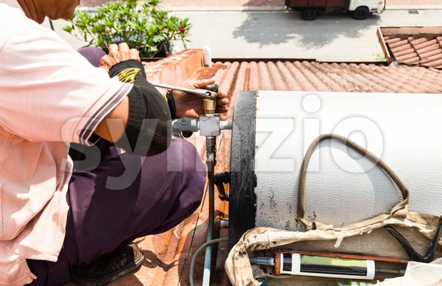 Closeup of worker fixing solar water heater on top of roof during maintenance work
