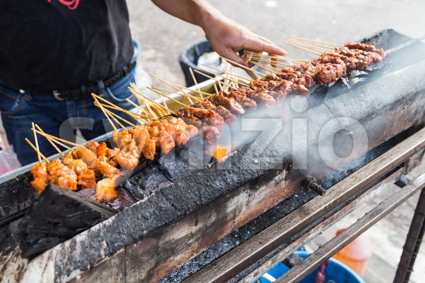 Vendor preparing chicken and beef barbecue satay on charcoal grille Stock Photo