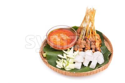 Barbecue satay served on traditional rattan plate with banana leaf Stock Photo