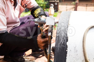 Closeup Worker fixing solar water heater on roof during maintenance Stock Photo