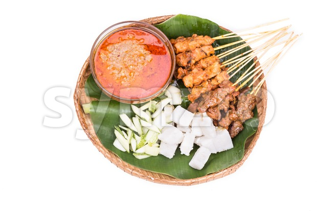 Freshly barbecue chicken and beef satay with gravy, rice, cucumber and onion served on traditional rattan weaved plate with banana ...
