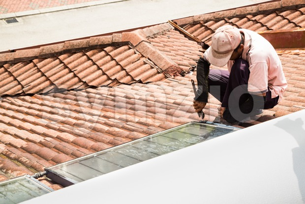 Worker fixing solar water heater on top of roof during maintenance work