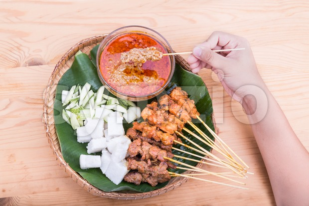 Hand  holding freshly barbecued chicken satay served with gravy, rice, cucumber and onion on traditional rattan weaved plate with ...